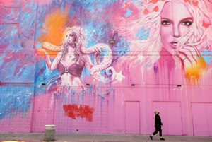 A woman, masked against COVID-19, walks past a building that features the image of Britney Spears at a shopping center in the Fairfax District in Los Angeles on May 18, 2020. Image: Genaro Molina/Los Angeles Times via TNS