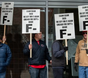 Chicago firefighters picket in front of the city's public safety headquarters in protest of problems during a recent promotional exam. (Photo/Zbigniew Bzdak, Chicago Tribune)