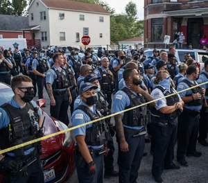 Officers stand near crime scene tape after an argument erupted between police and residents at the scene of an OIS in the Englewood neighborhood on Aug. 9, 2020, in Chicago.