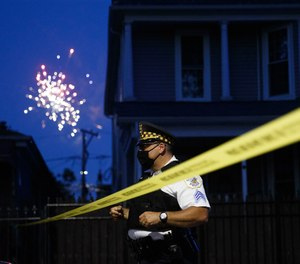 Officer Rocco Alioto works the scene where a 7-year-old girl was fatally shot along with a 32-year-old man on the 100 block ofNorth Latrobe AvenueonJuly 4, 2020inChicago.