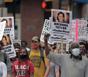 People walk in downtown Baltimore during a protest regarding the lack of charges brought against Louisville police in the killing of Breonna Taylor Sat., Sept. 26, 2020.