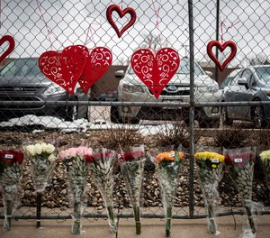Flowers are seen at a fence outside the location where a gunman opened fire at King Soopers grocery store on Monday on March 23, 2021, in Boulder, Colorado. Ten people were killed in the attack.