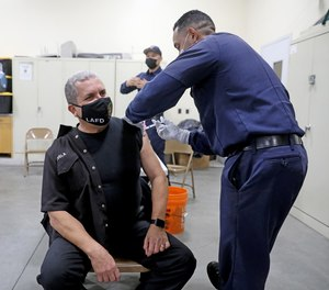 Los Angeles Fire Department (LAFD) Fire Inspector John Novela receives a Moderna COVID-19 vaccine given by LAFD Firefighter-Paramedic Mario Guillen. LAFD Chief Ralph M. Terrazas reported a