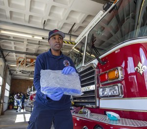 Firefighter Garry Helm displays a helmet shield meant to help limit the spread of COVID-19. Image: Joe Difazio/The Patriot Ledger