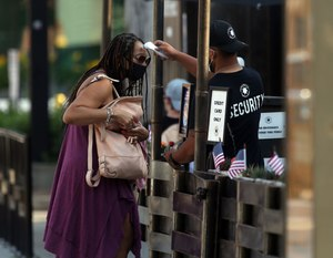 As restrictions on restaurants are eased, a worker takes a woman's temperature before she can enter Federales restaurant in Chicago on July 1, 2020. The Georgia bill would require businesses to do their part to operate safely in order to be shielded from COVID-related lawsuits. Image: 	Terrence Antonio James/Chicago Tribune via TNS