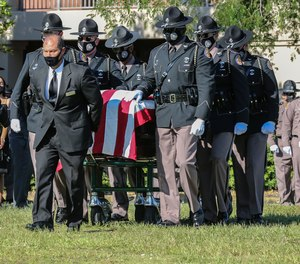 Florida Highway Patrol Honor Guard escort the casket of Trooper Lazaro R. Febles at Woodlawn Park Cemetery in southwest Miami-Dade on Friday, August 20, 2021. Febles served more than 11 years with the Florida Highway Patrol in Troop E Miami, he died of complications from COVID-19. (