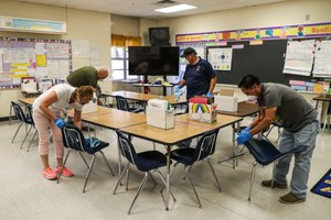 Austin district custodians deep clean Galindo Elementary School in March amid the coronavirus outbreak. The school district spent $7 million in the first six weeks after schools shuttered in coronavirus-related expenses like disinfecting building, protective equipment and purchasing technology for online learning. Image: Lola Gomez/American-Statesman via TNS