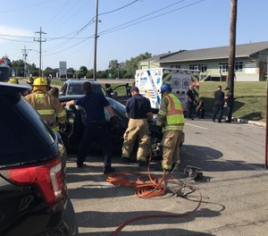 Erie firefighters work to free the occupants of a BMW sedan following a three-vehicle crash involving a Millcreek Paramedic Service ambulance, background, at the intersection of West 12th Street and Greengarden Road late Sunday afternoon. [Photo/Tribune News Service by Tim Hahn, Erie Times-News]