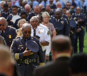 New interim Detroit Police Chief James White (center) bows his head during a 9/11 memorial service at Campus Martius Park in downtown Detroit.