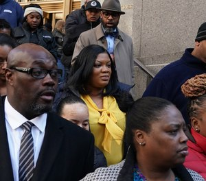 In this photo from November 25, 2019, Metropolitan Correctional Center guard Tova Noel (yellow shirt) surrounded by supporters leaves Federal Court in New York City.