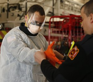 Green Fire Chief Jeff Funai, right, puts gloves on Sam Sprankle, a firefighter-paramedic with the Green Fire Department at Fire State 1 as Sprankle demonstrates the personal protective equipment EMS will wear while working with COVID-19 patients Wednesday, March 18, 2020 in Green, Ohio. (Photo/Karen Schiely, Beacon Journal)