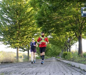 Former Woodstock firefighter Ryan Mains (right) runs with pace runner Leann McMonigan along the Fox River Trail, May 30, 2020 in Elgin, Illinois. After months of training, he was completed an 80-mile run to raise $18,000 to help first responders struggling with PTSD.
