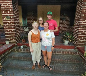 Faith and William Hunt stand outside their damaged home with daughters Grace, left, and Cana on Wednesday. The Hunt home was one of three fires believed to be arson.