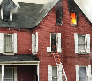 A firefighter became briefly trapped on the third floor of a burning duplex on Thursday. The firefighter managed to escape injury and continued fighting the blaze after being evaluated.