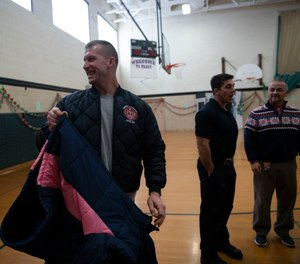 Rich Lutton along with other Jackson firefighters help students try on new coats at Frost Elementary School Friday Dec. 10, 2019. Members of the Jackson Fire Department gave out a total of 110 coats at Frost Elementary School. (Photo/Nicole Hhester, MLive.com)