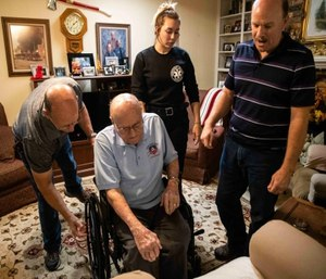 From left, Emmett Glosson's son, Joe, his great-grandaughter Tiffany Gell, and grandson Kevin Gell, help Emmett sit in his wheelchair at his home in Austin on Oct. 9. (Photo/Lola Gomez with the Austin American-Statesman)