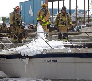 Firefighters work to put out a fire on a 41-foot boat on the New River in Fort Lauderdale. (Amy Beth Bennett/Sun Sentinel/TNS)