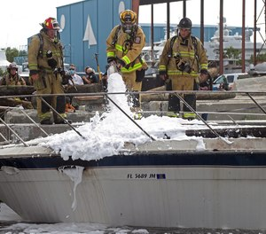 Firefighters work to put out a fire on a 41-foot boat on the New River in Fort Lauderdale.