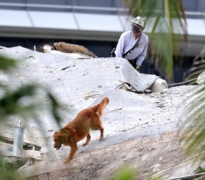 Fire rescue personnel conduct search and rescue with dogs in the rubble at Champlain Towers South Condo in Surfside, located at 8777 Collins Avenue, a part of which collapsed in the early morning in Surfside, Florida, Thursday, June 24, 2021.