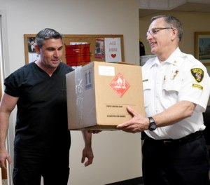 Rosario Carcione, pharmacy manager at Compounding Pharmacy of Green, drops off donated hand sanitizer to Canton City Fire Chief Tom Garra on Monday to help keep the department safe during the coronavirus pandemic. Monday, April 6, 2020. (Photo/Julie Vennitti, CantonRep.com)