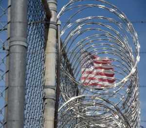 The American flag seen behind barbed wire at Holman Correctional Facility on Oct. 22, 2019. (Photo/Brian Lyman of Montgomery Advertiser via TNS)