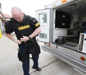 Lieutenant Michael Mohr, a Green Fire paramedic, suits up with the gear he wears while working as tactical paramedics with the Summit County Sheriff Department SWAT team in Green. Mohr and the other tactical paramedics wear the same uniform as the other SWAT members. (Photo/courtesy Mike Cardew/Beacon Journal)
