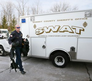 Green Fire Lt. Michael Mohr carries the gear he wears when working as a tactical paramedic for the SWAT team. (Photo/Mike Cardew, Beacon Journal)