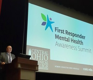 Kevin Reardon, a former firefighter with the Columbus Division of Fire and director of Central Ohio Technical College's Institute for Public Safety in Newark, welcomes about 130 attendees to the First Responder Mental Health Awareness Summit. (Photo/Holly Zachariah via Tribune News Service)