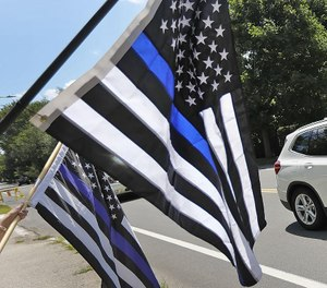 "A car passes supporters of law enforcement holding ""thin blue line"
