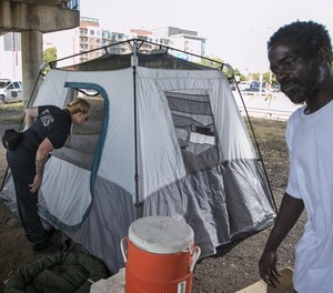 Amber Price, a community health paramedic and founding member of the city's Homeless Outreach Street Team, checks on a homeless woman in a tent under Interstate 35 at Cesar Chavez Street. At right is Doug Huddleston, who also lives under the overpass. (Photo/Tribune News Service by Jay Janner, American-Statesman)
