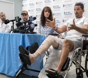 Hunter James Boyce explains how a gator that bit him had his leg in its mouth. Boyce spoke Tuesday during a press conference at St. Mary's Medical Center in West Plam Beach. His wife, Terisa Boyce, left, Danny McClellan and trauma Dr. Jorge Vega joined Boyce at the press conference.