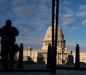 National Guard troops stand behind security fencing with the dome of the U.S. Capitol Building behind them on Saturday, Jan. 16, 2021, in Washington, D.C.