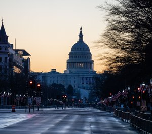 The sun rises behind the U.S. Capitol Building, seen from Pennsylvania Avenue, which is within the secure area around downtown Washington, D.C., on Saturday, Jan. 16, 2021.