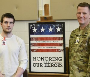 Jason Ricci, left, and Jeremy Degeier with a painting honoring Chief Warrant Officer 2 James A. Rogers Jr., who died in a helicopter crash in December. (Photo/Zachary Dwyer of St. Cloud Times via TNS)