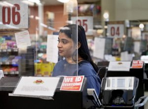 Rehanna Hussain, front-end store manager, is shielded by a protective barrier at the checkout register at Dave's Markets grocery store in Ohio City on Thursday, April 2, 2020. Image: Lisa DeJong/The Plain Dealer