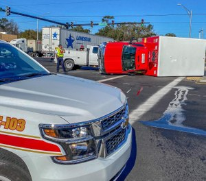 A Jacksonville Fire and Rescue truck was knocked onto its side in a collision on Tuesday. (Photo/Dan Scanlan, Florida Times-Union)
