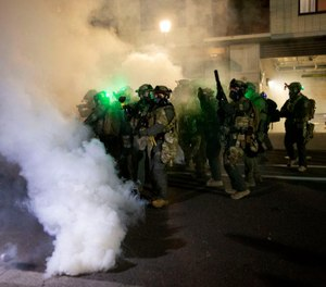 Federal agents use crowd control munitions, including tear gas, to clear out protesters from outside of the ICE building in South Portland. October 6, 2020. (Beth Nakamura/Staff)