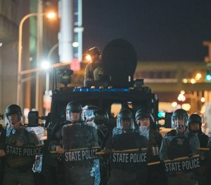 Police officers stand in front of an armored vehicle on Wednesday, September 23, 2020 in Louisville, Kentucky. (Jon Cherry/Getty Images/TNS)
