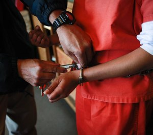 A new arrival at Camp Kenyon Scudder has her handcuffs removed after arriving at the girls detention center in Santa Clarita, Calif., on February 27, 2013.