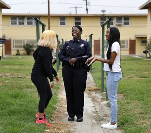 Newly appointed LAPD Deputy Chief Emada Tingirides, center, chats with two teenagers at Nickerson Gardens in Watts on Thursday, July 23, 2020. (Christina House/Los Angeles Times)
