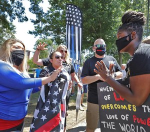 Protester Anne Pungitore (left) talks with counter-protester Tru Edwards at a demonstration outside Hingham Town Hall on Tuesday. More than 100 people, including several firefighters, gathered to protest the town's order for firefighters to remove the