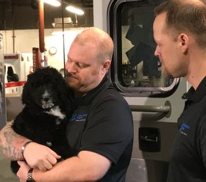 Hope, an 11-week-old golden doodle, is AMR's new therapy service dog. Her handlers include AMR operations supervisors Dusty VanderMeer, left, and Carl Hartman, right. (Photo/Justin P. Hicks, MLive.com)