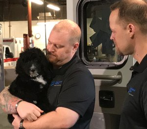 Hope, an 11-week-old golden doodle, is AMR's new therapy service dog. Her handlers include AMR operations supervisors Dusty VanderMeer, left, and Carl Hartman, right.