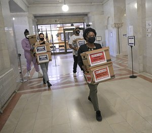 Corenia Smith, campaign manager with Yes 4 Minneapolis, carries boxes of signed petitions calling for replacing the Minneapolis Police Department with a new public safety department.