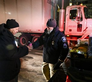 Sub. Minneapolis Police Sgt. Grant Snyder handed a cup of hot chocolate to Dawone Boclair outside the public library in downtown Minneapolis Tuesday night.