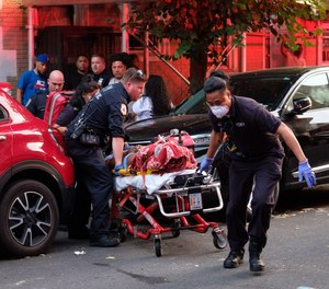 Medics remove a victim following a triple shooting on East 171st Street and College Avenue in the Bronx, New York City, on Sunday, July 5, 2020.