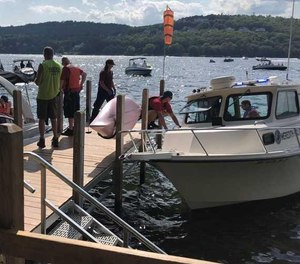 First responders meet Officer Joe Ponzo at a dock after he helped save a pilot who crashed his plane into Lake Winnipesaukee in New Hampshire on Sunday, Aug. 9, 2020.