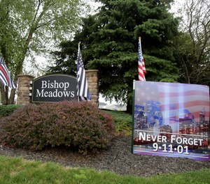 The entryway to Bishop Meadows neighborhood in Perry Township is donned with U.S. flags to honor 9/11.