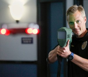 """Oceanside police officer Mark Bussey, who is with the Harbor Unit, aims the """"drone killer,"""" which brings the drone back to the ground by hitting it with radio waves that breaks the drone operator's command and control connection, as he demonstrates the device while in the lobby of the Oceanside Police Department in Oceanside on April 4, 2018. (Hayne Palmour IV/San Diego Union-Tribune/TSN)"""