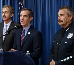 Los Angeles Mayor Eric Garcetti, center, flanked by Los Angeles City Attorney Mike Feuer, left, and LAPD Chief Charlie Beck, during a press conference detailing a court ruling against the Trump administration regarding its efforts to withhold federal grants from jurisdictions over their immigration enforcement policies on Thursday, April 12, 2018 at City Hall in Los Angeles, Calif.